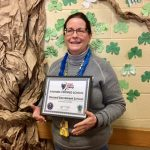 Teacher receiving kindness certified school award.