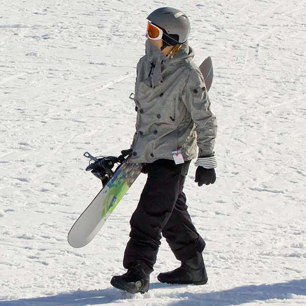 Snowboarder holding snowboard.