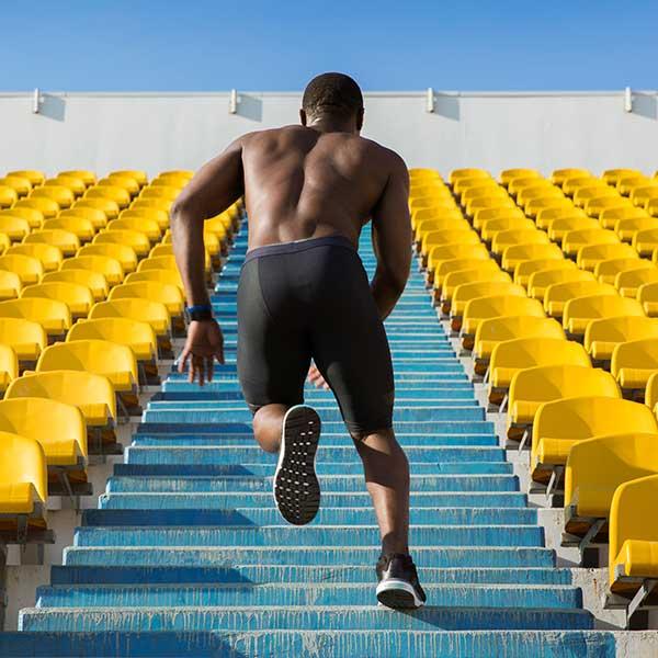 Man running up stairs at sports stadium.