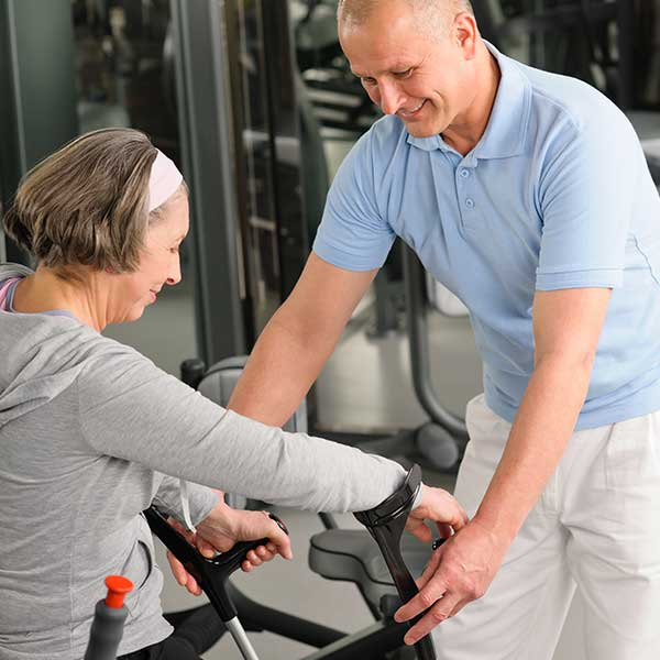 Physical therapist helping women do exercise.